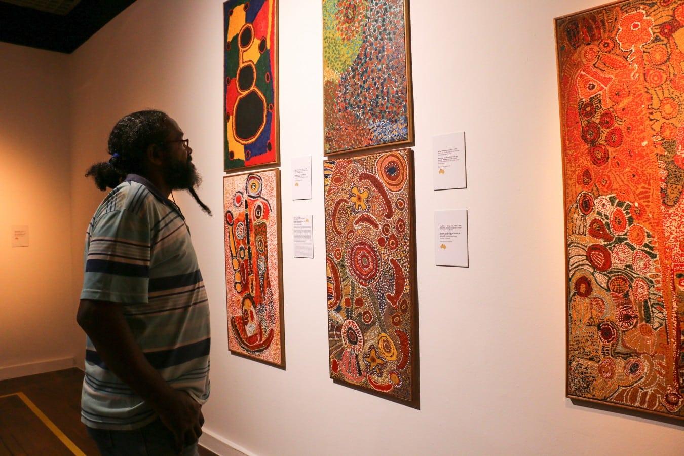 Visitante observa as obras dos artistas aborígenes de Balgo Hills. Essas obras são intituladas como a arte do Isolamento. Fotografia  Emmanuelle Bernard.  - O Tempo dos Sonhos: Arte Aborígene na Caixa Cultural