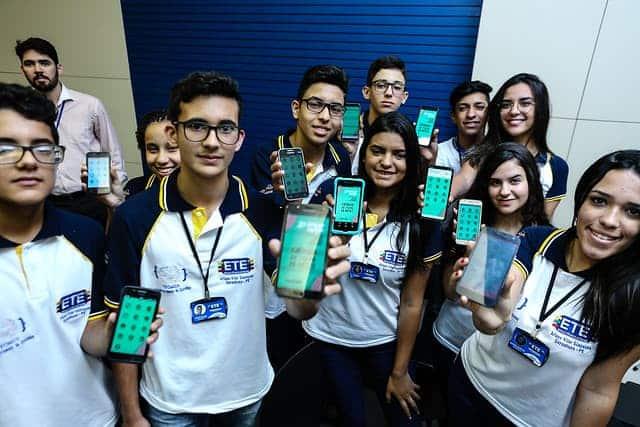 Imagem de um grupo de estudantes com celular na mão mostrando o app Fenearte 2019