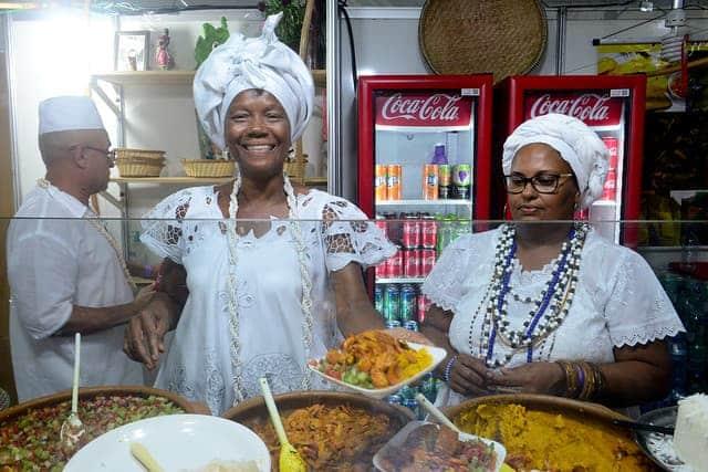 Imagem de uma baiana vendendo acarajé no estande da Praça
