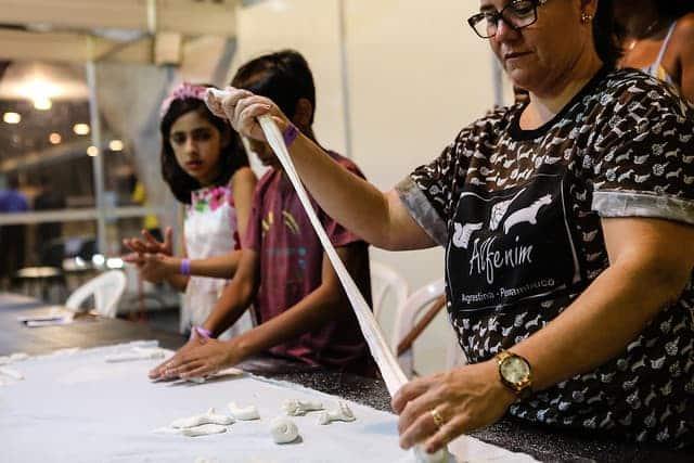 Orientadora ensinando crianças a fazer alfenim na Fenearte 2019