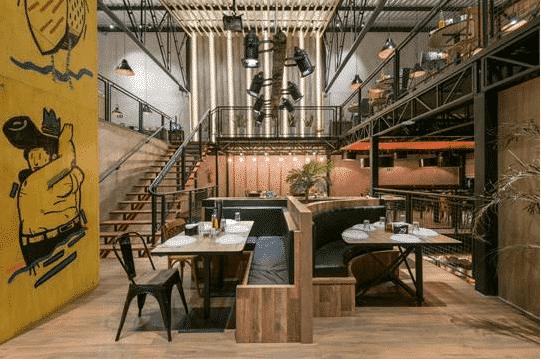 Restaurante com desenhos nas paredes, refletores, poltronas em paletes