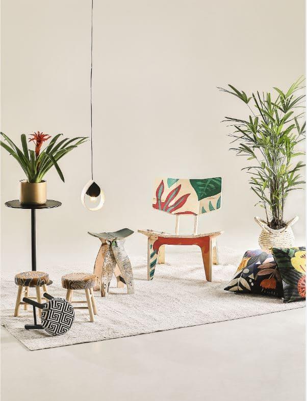 Ambiente montado na feira com tapetes, bancos e almofadas coloridas