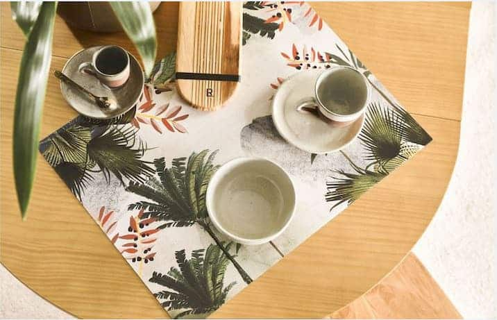 Mesa em madeira com jogo americano e xícaras com motivos tropicais